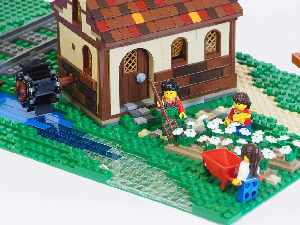 man and woman lego bricks with house and garden